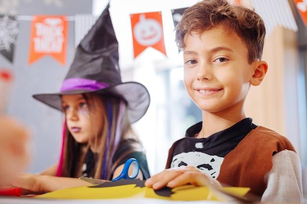 Spelen op de kleuterschool. leuke ijverige donkerharige jongen die halloween-kostuum draagt en met andere kinderen in de kleuterschool speelt
