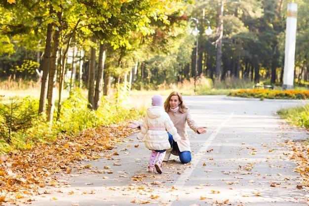 Spelen tegen wazig gele bladeren in herfst park en gelukkige familie