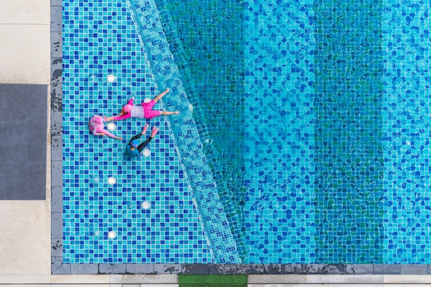 Spelende kinderen in het zwembad, luchtfoto bovenaanzicht