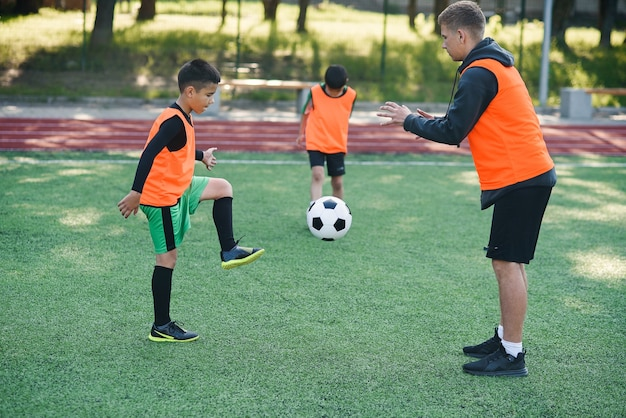 Speler in voetbal uniforme uitwerking van de schoppen bal met coach op stadion