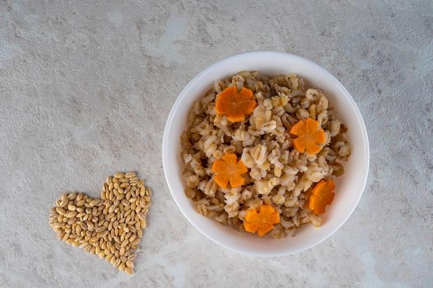 Speltpap in een witte kom en versierd met een asteriskwortel, dieetvoeding.
