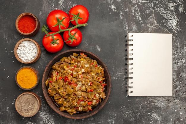 Sperziebonen en kruiden sperziebonen in de kom naast het witte notitieboekje en de kommen met kruiden en tomaten met stengels op de donkere tafel