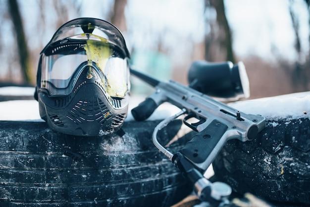 Spetterde paintball masker met bril en marker pistool close-up, niemand. extreme game-uitrusting, sportmunitie