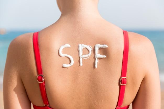 Spf woord gemaakt van sunblock op de rug van de vrouw op het strand. zonbeschermingsfactor concept.