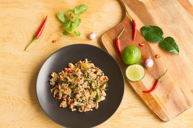 Spicy minced duck salad in een zwarte plaat op een houten tafel