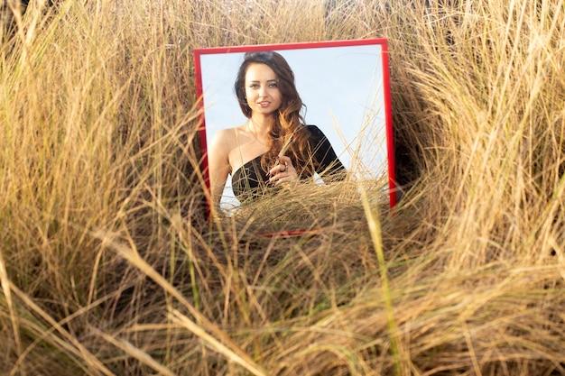 Spiegel in het gras die het meisje weerspiegelt portret van een meisje met lang haar in de spiegel