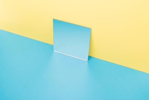 Spiegel op blauwe tafel geïsoleerd op geel