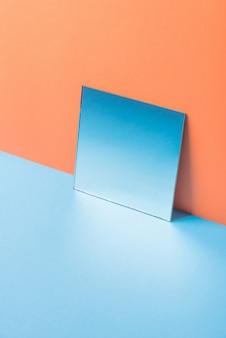 Spiegel op blauwe tafel geïsoleerd op oranje