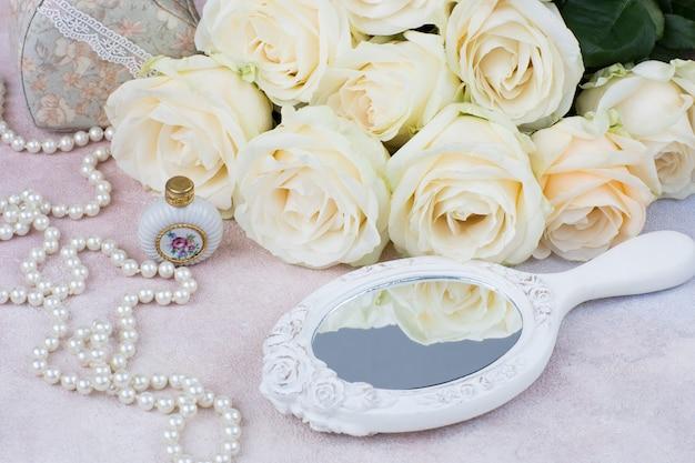 Spiegel, parel kralen, parfum, kistje en een boeket witte rozen