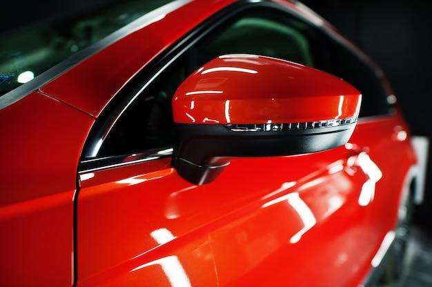 Spiegel van mooie en nieuwe oranje sport suv auto in moderne garage.