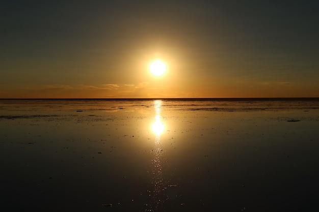 Spiegeleffect van de ondergaande zon bij uyuni salt flats of salar de uyuni in bolivia, zuid-amerika