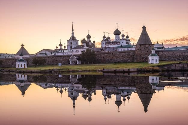Spiegelreflecties van het solovetsky-klooster in het kalme water van de bay of prosperity op de solovetsky-eilanden onder de roze dageraad