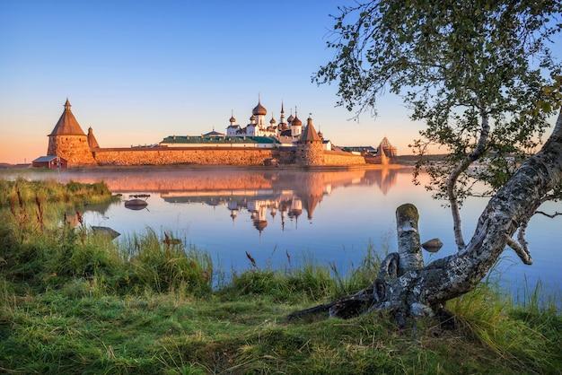 Spiegelreflecties van het solovetsky-klooster in het kalme water van het heilige meer op de solovetsky-eilanden in het licht van de dageraadzon en een berk aan de kust