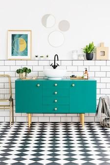 Spiegels en poster boven groene kast in badkamer interieur met gouden stoel en planten. echte foto