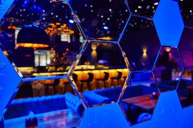 Spiegels in de vorm van vele zeshoeken waarin de nachtclub weerspiegeld wordt
