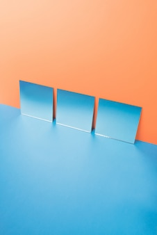 Spiegels op blauwe tafel geïsoleerd op oranje