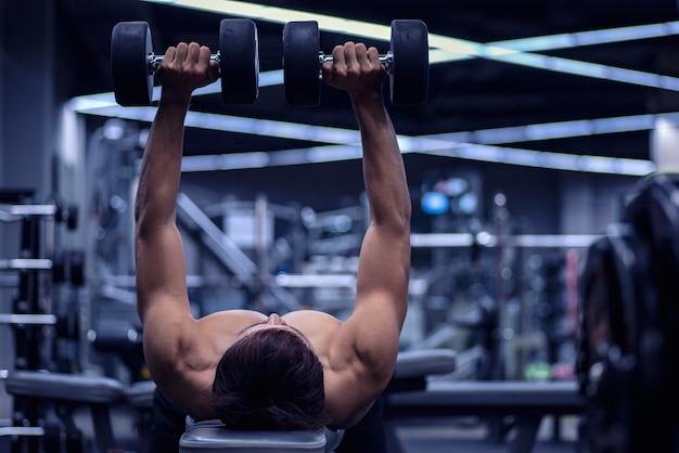 Spierbodybuilderkerel die oefeningen met domoor over blauwe achtergrond doen