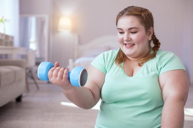 Spieren winnen aan. mollige jonge vrouw met halter zittend op de yogamat