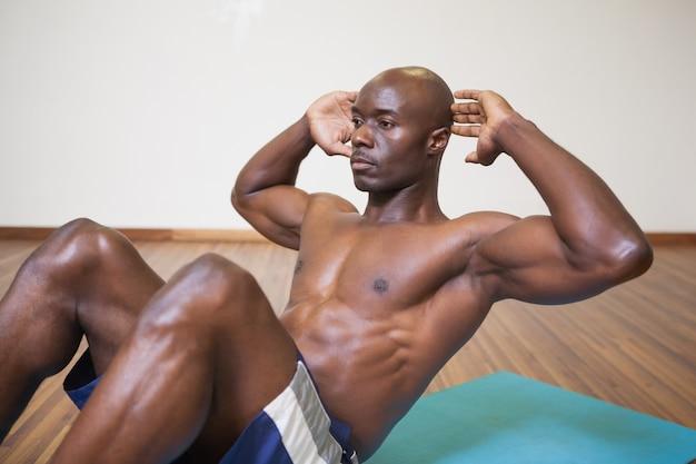 Spiermens die buikkraken in gymnastiek doen