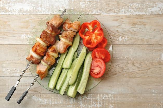 Spies van gekookt varkensvlees op spiesjes - met uien
