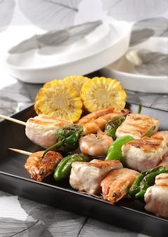 Spies van groene paprika en garnalen tonijn met garnituur van gestoofde maïs op een grijze plaat