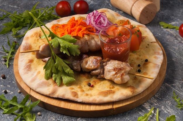 Spies van varkensvlees op pitabroodje met groenten en tomatensaus. horizontaal frame