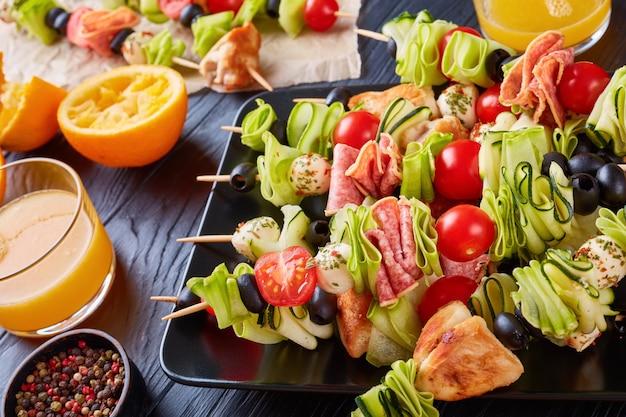 Spiesjes met kippenvlees, courgette, tomaten, mozzarella balletjes, plakjes salami, olijven op een zwarte plaat op een houten tafel met sinaasappelsap in glazen bekers, zomerpicknick recept, close-up