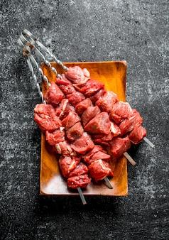 Spiesjes met rauwe kebab op houten plaat op zwarte houten tafel