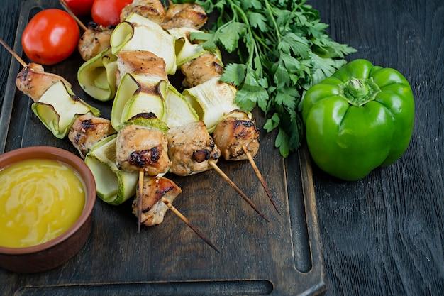Spiesjes op een spies met courgette met saus en groenten op een snijplank