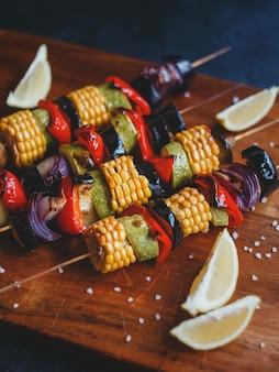 Spiesjes van gegrilde groenten, maïs, courgette, champignons, rode peper