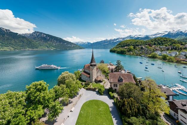 Spiez-kasteel met zeilboot op meer thun in bern, zwitserland.
