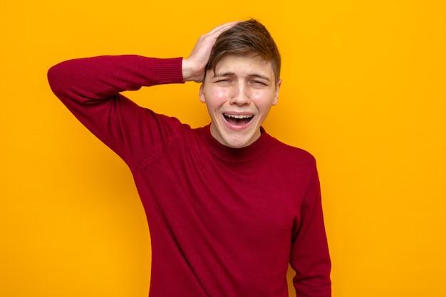 Spijt dat hij zijn hand op zijn hoofd legt, jonge knappe kerel met een rode trui geïsoleerd op een oranje muur