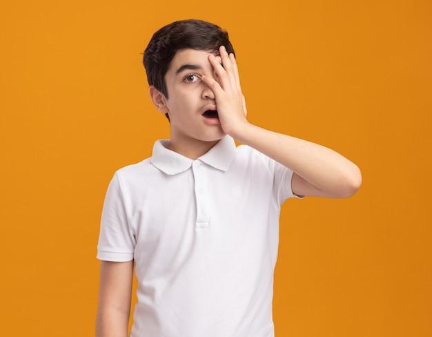 Spijt hebben van jonge blanke jongen die de helft van het gezicht met de hand bedekt