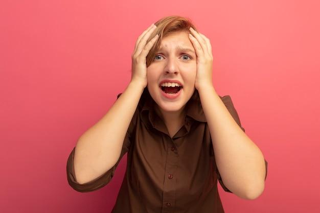 Spijt van een jong blond meisje dat de handen op het hoofd houdt en er geïsoleerd op een roze muur uitziet?