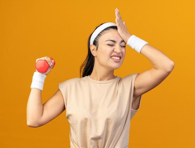 Spijt van een jong kaukasisch sportief meisje met een hoofdband en polsbandjes die een halter opheft die de hand op het hoofd houdt met gesloten ogen geïsoleerd op een oranje muur