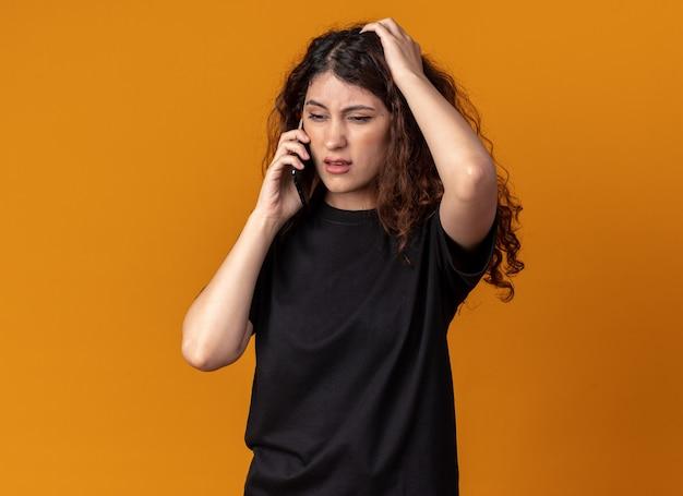 Spijt van een jong mooi meisje dat aan de telefoon praat en de hand op het hoofd houdt en naar beneden kijkt