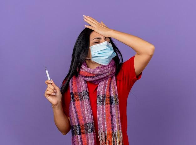 Spijt van jong kaukasisch ziek meisje met masker en sjaal met thermometer hand op het hoofd zetten met gesloten ogen geïsoleerd op paarse muur met kopie ruimte