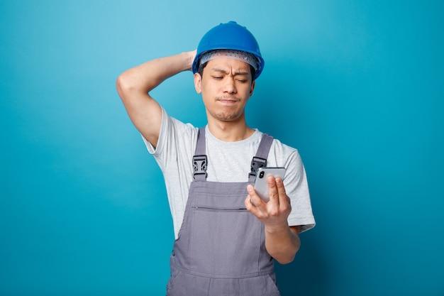 Spijt van jonge bouwvakker die veiligheidshelm en uniform draagt die hand achter hoofd houden en mobiele telefoon bekijken