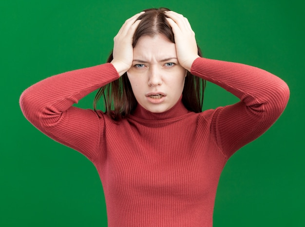 Spijt van jonge mooie vrouw die naar de voorkant kijkt en de handen op het hoofd houdt geïsoleerd op de groene muur