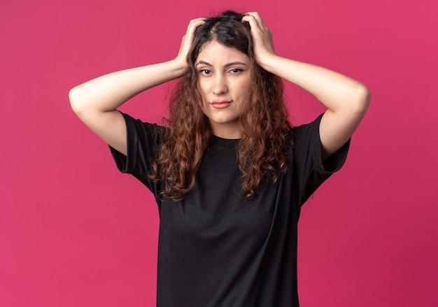 Spijt van jonge mooie vrouw die naar de voorkant kijkt en de handen op het hoofd houdt geïsoleerd op de karmozijnrode muur?