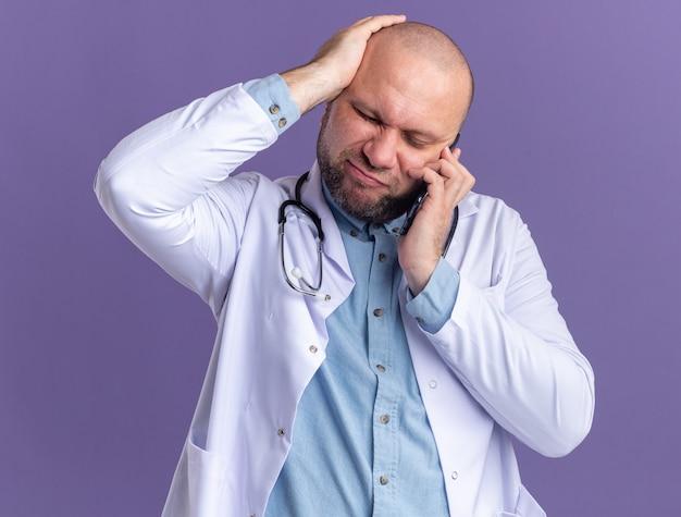 Spijt van mannelijke arts van middelbare leeftijd met een medische mantel en een stethoscoop die aan de telefoon praat en de hand op het hoofd houdt met gesloten ogen geïsoleerd op de paarse muur