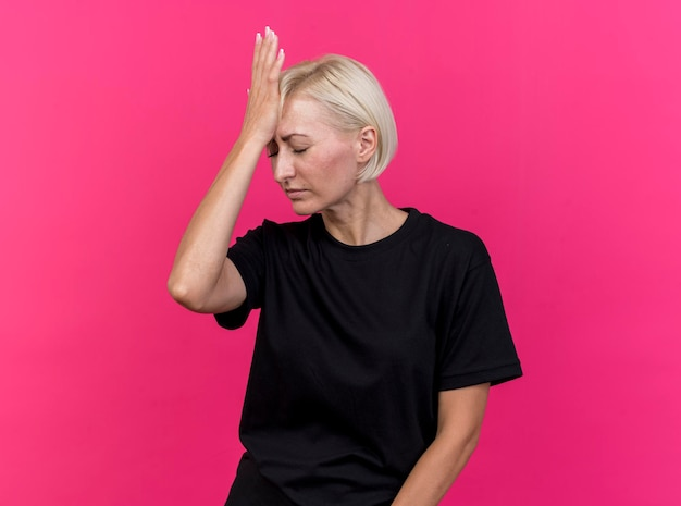 Spijt van middelbare leeftijd blonde slavische vrouw die hand op het hoofd houdt met gesloten ogen geïsoleerd op roze muur met kopie ruimte
