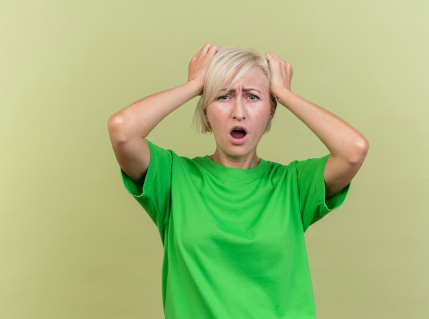 Spijt van middelbare leeftijd blonde slavische vrouw kijken camera handen op het hoofd geïsoleerd op olijfgroene achtergrond met kopie ruimte te kijken