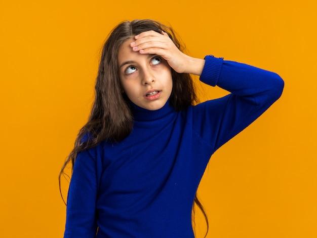 Spijt van tienermeisje dat hand op het voorhoofd houdt en omhoog kijkt geïsoleerd op oranje muur