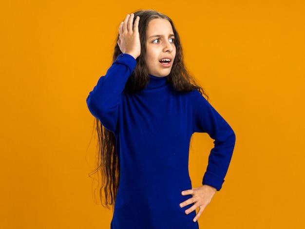 Spijt van tienermeisje dat naar de zijkant kijkt en de hand op de taille en op het hoofd houdt geïsoleerd op een oranje muur met kopieerruimte