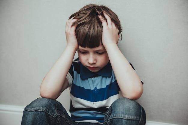 Spijt van trieste kleine jongen die alleen zit, eenzaamheid, gestrest depressief kind huilend met depressie, angst, problemen met geestelijke gezondheid, eenzame jongen met handen op het hoofd, hikikomori-syndroomziekte