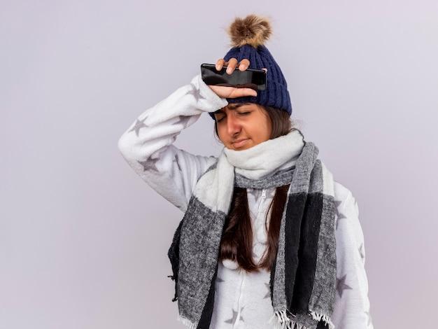 Spijt van ziek meisje met gesloten ogen dragen winter hoed met sjaal telefoon houden en zetten arm op voorhoofd geïsoleerd op witte achtergrond