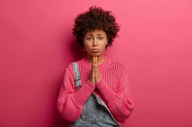 Spijtige donkere afro-amerikaanse vrouw smeekt om vergeving, voelt zich schuldig, portemonneert onderlip, draagt gebreide trui, geïsoleerd op roze muur, smeekt ouders om geld, ziet er onschuldig uit