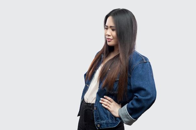 Spin- of nierpijn. profiel zijaanzicht portret van mooie brunette aziatische jonge vrouw in casual blauw denim jasje staande en haar rug aan te raken. studio opname, geïsoleerd op lichtgrijze achtergrond.