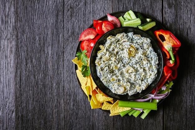Spinazie artisjok bladkaas doop in een kom met tortilla chips, komkommer, stengels bleekselderij, plakjes tomaat en rode paprika, horizontale weergave van bovenaf, plat leggen, vrije ruimte